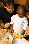 Preschool introductory period children visit classrooms with parents for shortened day in small groups young male teacher working with male student on task, how to roll play dough