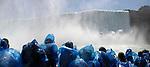 People in blue rain coats enjoying Canadian Horseshoe Niagara Falls view from Maid of the Mist Boat Ride