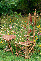 Rustic handmade furniture from red dogwood branches sits in field of native wildflowers