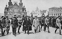 Valdimir Lenin with a group of commanders bypasses the front of the universal education troops in Red Square, 1917.