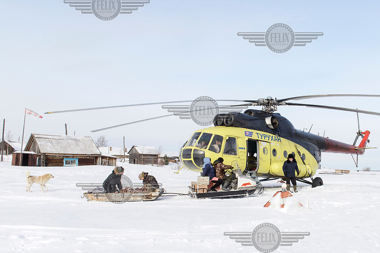 A patient, with a paramedic, are transported on a snowmobile from their house to the helicopter which will fly them to hospital.