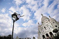 Street performer climbs up a lampost in front of the Basilica of the Sacré Coeur, Montmartre, Paris, France, 15 September 2009