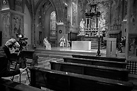 """Switzerland. Canton Ticino. Lugano. Easter in Cattedrale di San Lorenzo. The bishop Valerio Lazzeri celebrates the Sunday mass in an empty cathedral. The believers could not attend the religious service due to the coronavirus. A cameraman from the RSI is filming the service and it can be looked at on streaming on internet. Radiotelevisione svizzera di lingua italiana (RSI) is a Swiss public broadcasting organisation, part of SRG SSR.Valerio Lazzeri (born 22 July 1963) is a Swiss Roman Catholic bishop. Ordained to the priesthood on 2 September 1989, Lazzeri was named bishop of the Roman Catholic Diocese of Lugano, Switzerland on 4 November 2013. Easter, also called Pascha or Resurrection Sunday, is a festival and holiday commemorating the resurrection of Jesus from the dead, described in the New Testament as having occurred on the third day after his burial following his crucifixion by the Romans. The Diocese of Lugano is a branch of the Catholic Church immediately subject to the Holy See.  Due to the spread of the coronavirus (also called Covid-19), the Federal Council has categorised the situation in the country as """"extraordinary"""". It has issued a recommendation to all citizens to stay at home, especially the sick and the elderly. From March 16 the government ramped up its response to the widening pandemic, ordering the closure of religious services. 12.04.2020  © 2020 Didier Ruef"""