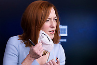 White House Press Secretary Jen Psaki removes a face mask to deliver remarks at a news briefing in the James Brady Press Briefing Room of the White House, in Washington, DC, USA, 10 February 2021.<br /> CAP/MPI/RS<br /> ©RS/MPI/Capital Pictures