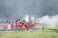 British redcoats, with drummers in rear, attack the Continental Army through a haze of smoke at a Revolutionary War encampment, Old Sturbridge Village, Massachusetts, USA.