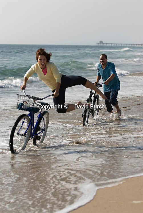 Mature woman jumping while man walking with bicycle at beach, smiling.