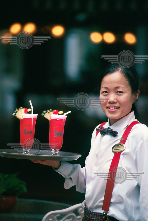 Waitress with the famous Singapore Sling cocktail at the Raffles Hotel. This refreshing drink was created at the hotel in 1915 by barman Ngiam Tong Boon.