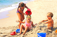 Children playing at beach in group and having fun on vacation holida