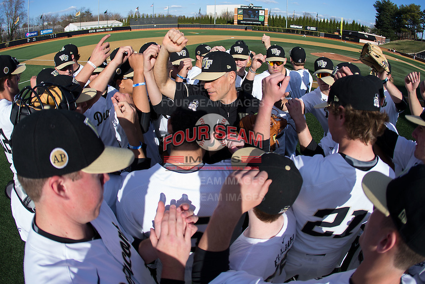 The Wake Forest Demon Deacons huddle around Wake Forest Demon Deacons head coach Tom Walter (center) prior to the game against the USC Trojans at David F. Couch Ballpark on February 24, 2017 in  Winston-Salem, North Carolina.  The Demon Deacons defeated the Trojans 15-5.  (Brian Westerholt/Four Seam Images)