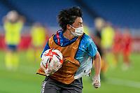 YOKOHAMA, JAPAN - AUGUST 6: A ball person runs with the ball during a game between Canada and Sweden at International Stadium Yokohama on August 6, 2021 in Yokohama, Japan.