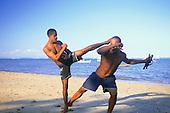Salvador, Brazil. Two young men practising capoeira martial art on the beach.