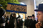 """A person holds up a sign that reads """"in G-d we trust"""" at a protest against COVID-19 restrictions in the Orthodox Jewish neighborhood Borough Park on Wednesday, October 7, 2020 in the Park in the Brooklyn borough of New York City.  Residents are protesting against new restrictions that would close schools, limit attendance at religious services and close non-essential businesses in areas with surges in COVID-19 cases.  Photograph by Michael Nagle"""