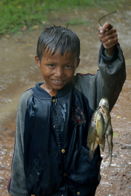 Young boy during a heavy tropical Monsoon rain shower with his catch of frogs and fish at Beng Mealea, Angkor area, Cambodia