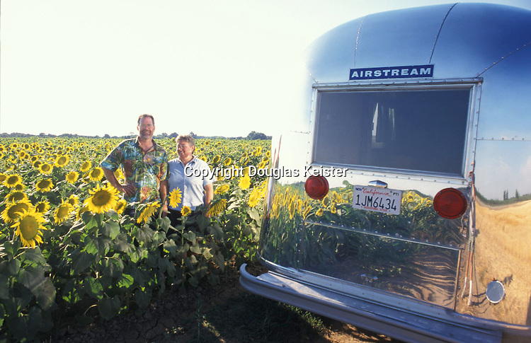 Arlen and Shirley Manning bask in the glow of their 1964 Airstream Globe Trotter in afield of sunflowers in Chico, California.