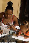 20 month old toddler baby girl drawing scribbling with pen imitation modeling as mother feeds infant brother and writes with pen