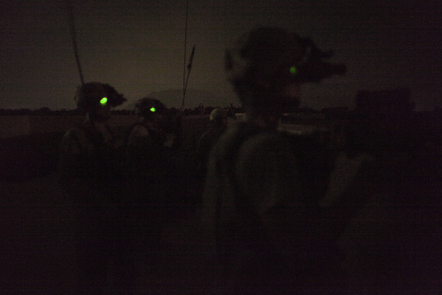 Soldiers donning night vision equipment watch a brief exchange of fire taking place at a nearby outpost from the roof of  Combat Outpost Fitzpatrick in Zhari District, Kandahar, Afghanistan. The violently contested district sits astride the strategically Highway 1 ringroad between Kandahar and Lashkar Gah and is seen by some as the birthplace of the Taliban movement.