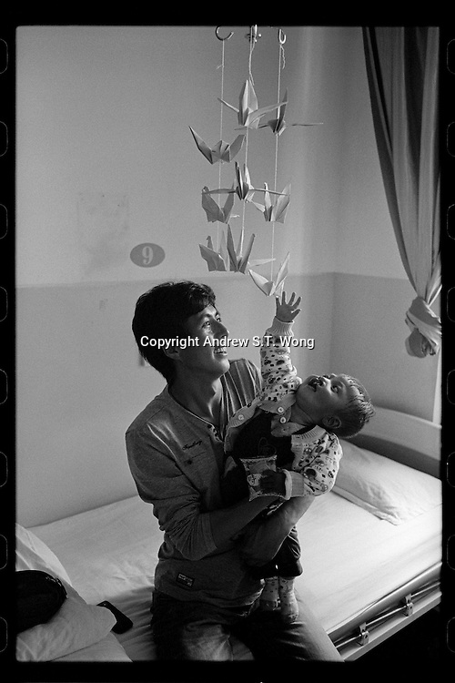 A Tibetan father plays with his young son before the boy's cleft lip operation organized by Smile Angel Foundation at a hospital in Xining, Qinghai province, China, August 2013. (Names withheld for privacy)