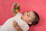 4 month old baby girl closeup on back holding toy with colored wooden rings
