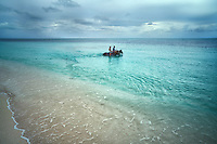 Woman and man riding horse in water. Turks and Caicos. Providenciales