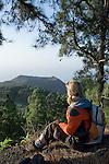 Spain, Canary Islands, La Palma, view at vulcano San Antonio near village Los Canarios Fuencaliente, woman with backpack hiking, taking a break