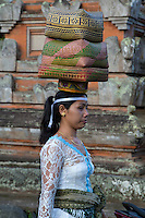 Bali, Indonesia.  Balinese Hindu Woman Carrying Offerings on her Head for the Temple.  Dlod Blungbang Village.