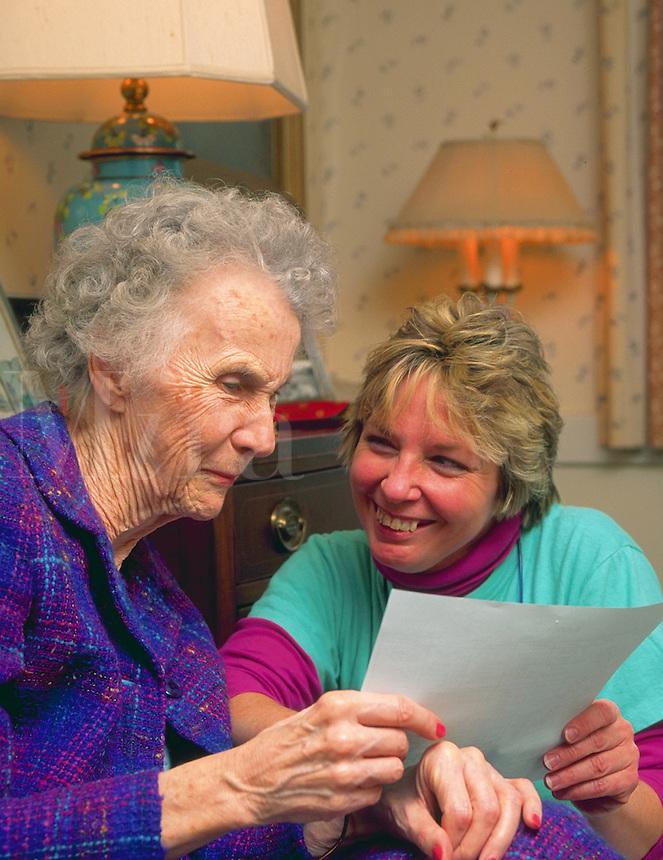 Portrait of a senior woman and smiling caregiver at a nursing home.