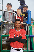 Batavia Muckdogs Brayan Hernandez (23) in the dugout posing with some young fans for a rain delay during a NY-Penn League game against the Auburn Doubledays on June 15, 2019 at Dwyer Stadium in Batavia, New York.  Batavia defeated Auburn 7-5.  (Mike Janes/Four Seam Images)