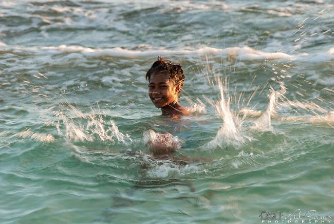 A boy splashing in the sea on Kiritimati island in Kiribati