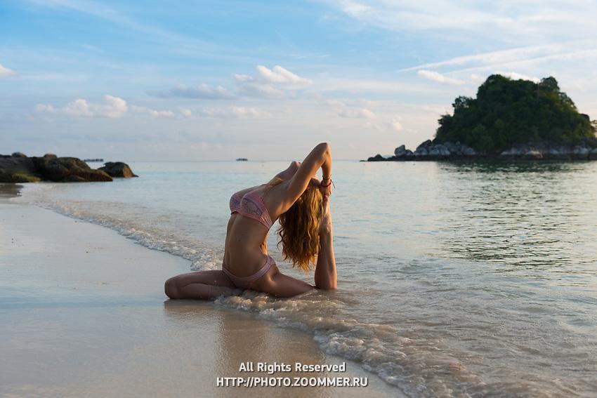 Girl in pigeon pose practicing beach yoga in Koh Lipe, Thailand