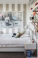 One of the three boys' rooms displays another work by Frank van Reenen, 'Truman with Bunnies'. The side tables and shelves were designed and made by Andrew Dominic.