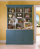 Pottery pieces and books are displayed on the shelves of a blue display unit with cupboard and drawer storage below.