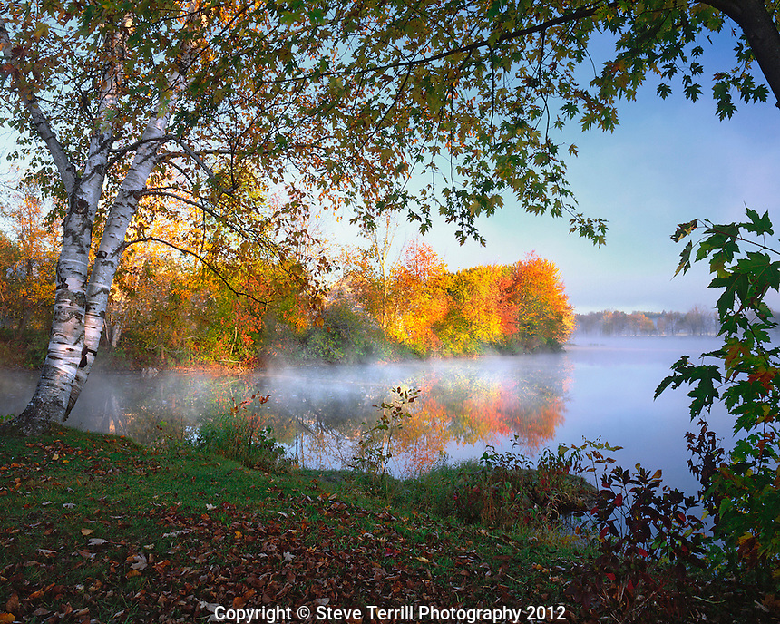 USA, Maine, Morning sun and fog rising from Douglas Pond in Somerset County near Pittsfield