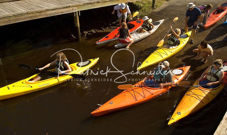 A group of kayakers launch their boats into the water in Amelia Island, FL
