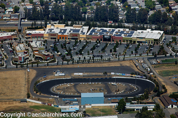 aerial photograph of the Petaluma Speedway at the Sonoma-Marin Fairgrounds.  The East Washington Place shopping center and US Highway 101 are in the background,  Petaluma, Sonoma County, California.