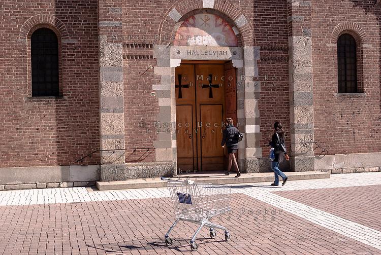 Sesto San Giovanni (Milano). Carrello della spesa abbandonato di fronte alla chiesa S. Maria Nascente --- Sesto San Giovanni (Milan). Abandoned shopping cart in front of a church