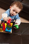 2 year old toddler boy at home playing with colorful wooden shapes and peg puzzle vertical