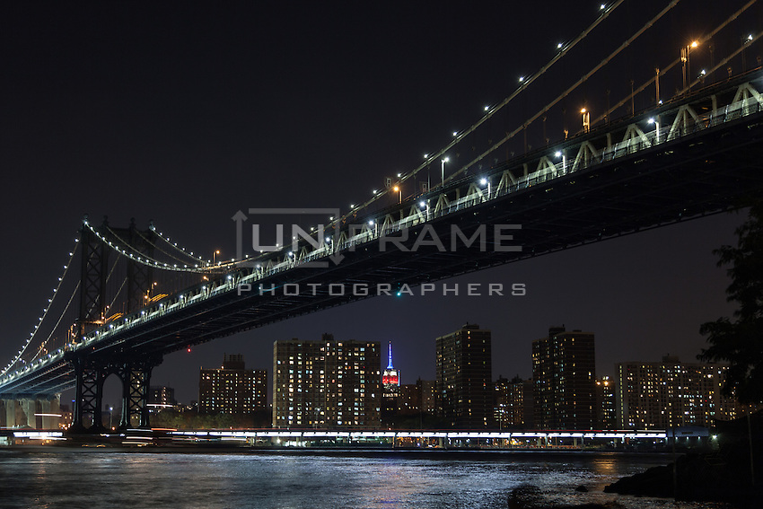 Manhattan Bridge and the Empire State light colored with the US American flag on the 13th anniversary of 9/11. View from Brooklyn Bridge Park.  Sept. 11, 2014. New York, USA.