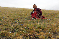 A young Tibetan monk on a hill overlooking the town of Sershul on the Tibetan Plateau, in western China. The town is home to a large monastery which houses thousands of monks. The Sanjiangyuan or Three Rivers Headwater region of western China contains the sources of the Yangtze, Mekong and Yellow Rivers.