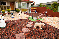 Retired Lawn; front yard lawn alternative with colored rock, whimsical Disney cartoon statuary and lwn mower