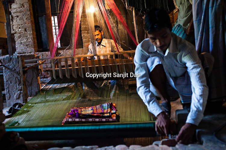 A family member helps Md. Naim with the silk threads in their workshop. Their family is one of the few muslim weavers using traditional looms to weave famous Benaresi saris in his workspace in Gazi Sadullahpura Bade Bazaar in Varanasi in Uttar Pradesh, India. Photograph: Sanjit Das/Panos