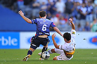MELBOURNE, AUSTRALIA - JANUARY 26, 2010: Leigh Broxham from Melbourne Victory is tackled by Troy Hearfield from Wellington Phoenix in round 19 of the A-league match between Melbourne Victory and Wellington Phoenix FC at Etihad Stadium on January 26, 2010 in Melbourne, Australia. Photo Sydney Low www.syd-low.com