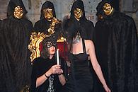 Girls wearing black masks holding a lit candle.