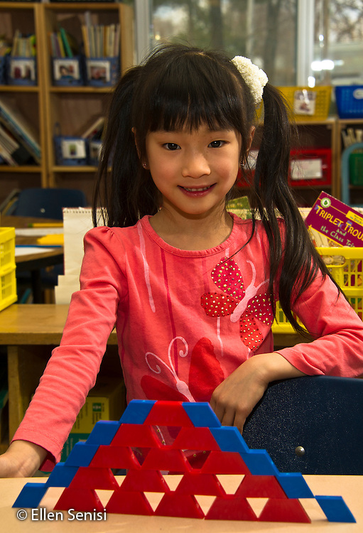 MR / Schenectady, New York. Paige Elementary School (urban public elementary school). First grade independent work at learning center time. Student (girl, 6, Chinese American) smiles with pride at structure she has built with shape pattern blocks. MR: Wil40. ID: AL-g1g. © Ellen B. Senisi.