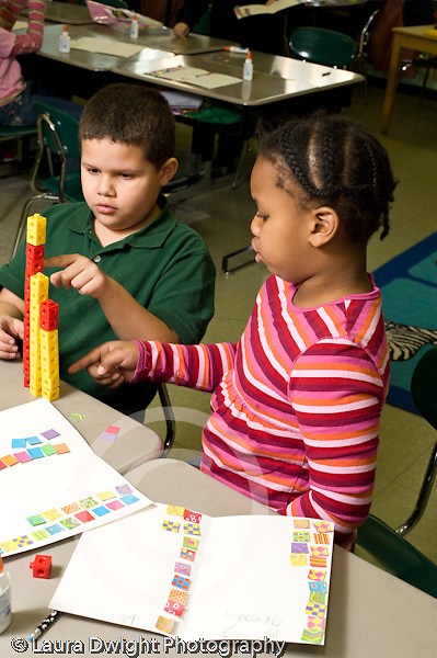 Education Elementary school Grade 1 mathematics hands on learning boy and girl counting and comparing rows of colored squares and rows of connected colored cubes vertical