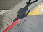 A shadow of a pedestrian waking the streets of Northbeach in San Francisco, California.