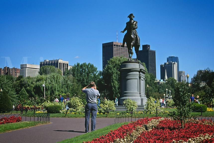Massachusetts, Boston; Tourists Photograph George Washington Monument; Boston Common; City Skyline In Backgroun