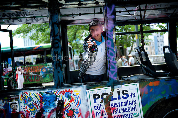 Copyright : Magali Corouge / Documentography<br />Istanbul, Turkey, the 8th of June 2013.<br /><br />A young boy is playing a colour bomb inside one of the numerous buses that have been burned.