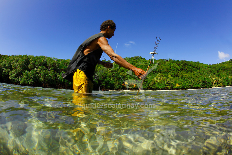 A local man fishing on the reef at Bagaman Island in the  Louisiade Archipelago..The Louisiade Archipelago is a string of ten larger volcanic islands frequently fringed by coral reefs, and 90 smaller coral islands located 200 km southeast of New Guinea, stretching over more than 160 km and spread over an ocean area of 26,000 km  between the Solomon Sea to the north and the Coral Sea to the south. The aggregate land area of the islands is about 1,790 kmu178  (690 square miles), with Vanatinai (formerly Sudest or Tagula as named by European claimants on Western maps) being the largest..Sideia Island and Basilaki Island lie closest to New Guinea, while Misima, Vanatinai, and Rossel islands lie further east..The archipelago is divided into the Local Level Government (LLG) areas Louisiade Rural (western part, with Misima), and Yaleyamba (western part, with Rossell and Tagula islands. The LLG areas are part of Samarai-Murua District district of Milne Bay. The seat of the Louisiade Rural LLG is Bwagaoia on Misima Island, the population center of the archipelago. .The Louisiade Archipalego is part of the Milne Bay province of Papua New Guinea..It lies between approximately 10 degrees south and 11.5 degrees south, and 151 degrees east and 154 degrees east. It is an area of Islands, reefs and cays some 200 nm long and 50 nm wide, stretching from the south east tip of mainland Papua New Guinea in a east south east direction..