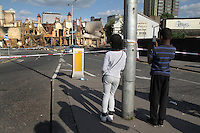 Children take a photograph with a mobile phone of the burnt out Reeves furtniture store in the London borough of Croydon. London saw the beginnings of riots on Saturday evening, after a peaceful protest in response to the shooting by police of Mark Duggan during an attempted arrest, escalated into violence. By the third night of violence, rioting and looting had spread to many areas of the capital and to other cities around the country.