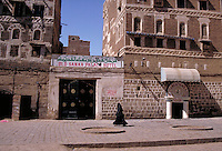 Woman in traditional long black dress with veil walks on the sidewalk in front of The Old Sanaa Palace Hotel, architecture, buildings. Yemen.